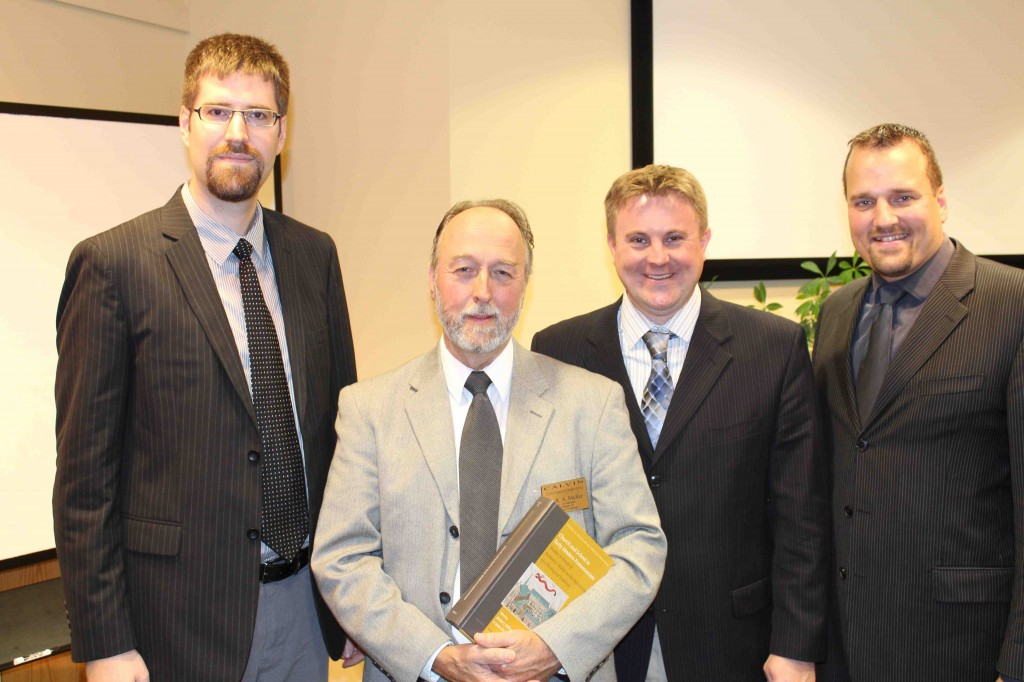 Richard Muller (holding book) stands with the editors of his Festschrift (from left to right): David S. Sytsma, Jordan J. Ballor, and Jason Zuidema